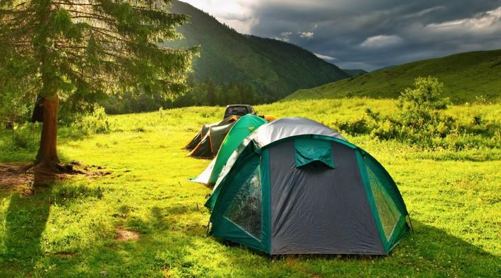 Туристическая палатка на поляне летом