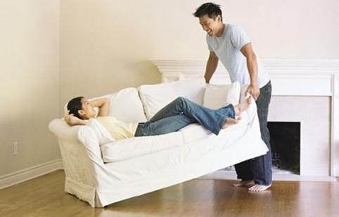 Мужчина переносит диван